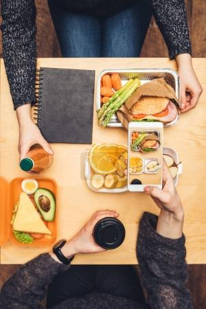 Photo pour Image recadrée de femme assise à table et de la prise de photo de déjeuner avec smartphone - image libre de droit