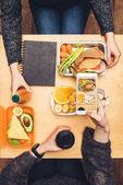 cropped image of woman sitting at table and taking photo of lunch with smartphone
