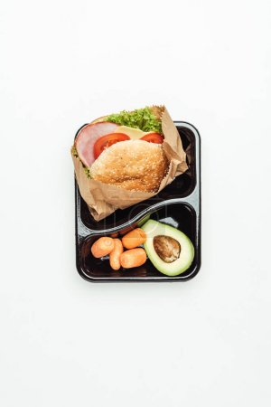 top view of lunch box with burger and vegetables isolated on white