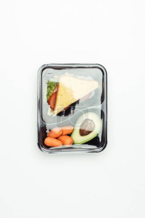 top view of closed plastic lunch box with sandwich and vegetables isolated on white