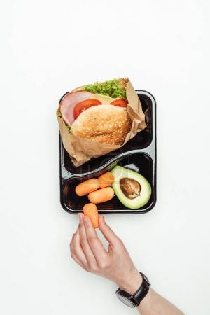 cropped image of woman taking carrot from take away container isolated on white