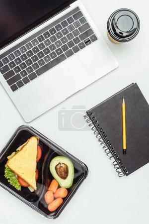 top view of laptop and food in lunch box isolated on white