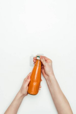 cropped image of woman opening bottle of carrot juice isolated on white