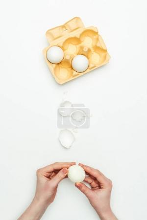 cropped image of woman peeling cooked egg isolated on white