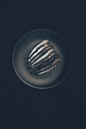 Top view of pile of fish in frying pan isolated on black