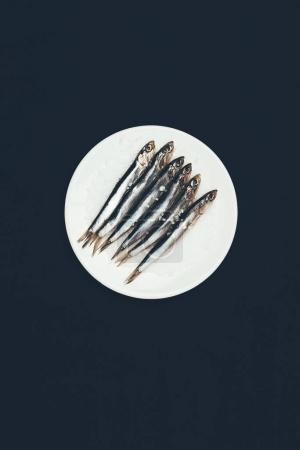 Top view of salted pile of fish in plate isolated on black
