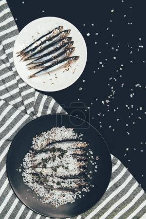 Top view of plate and frying pan with salted pile of fish and towel isolated on black
