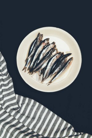 Top view of pile of fish in plate and towel isolated on black