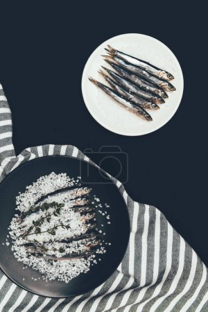 Salted pile of salted fish with rosemary in frying pan and plate with fish isolated on black