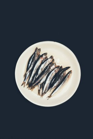Top view of pile of fish on plate isolated on black