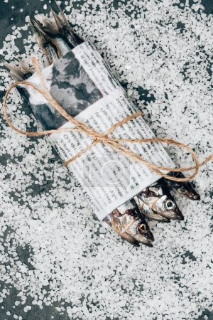 Top view of pile of fish in newspaper wrapped by string on surface covered by salt