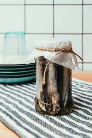 Pile of salted fish in jar wrapped by string on towel with plates and glass behind