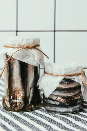 Pile of salted fish in jars wrapped by strings on towel