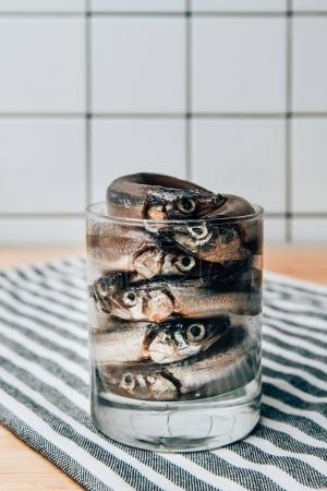 Front view of pile of salted fish in glass on towel