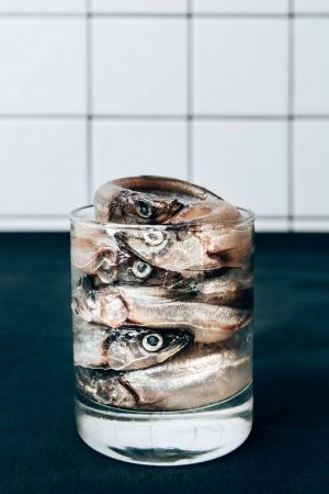 Front view of pile of salted fish in glass