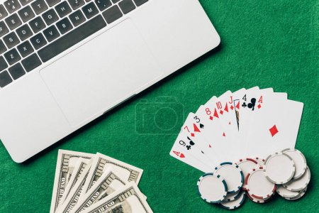 Online gambling concept with cards and money on table by laptop