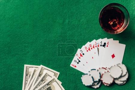 Money and cards with whiskey in glass on casino table