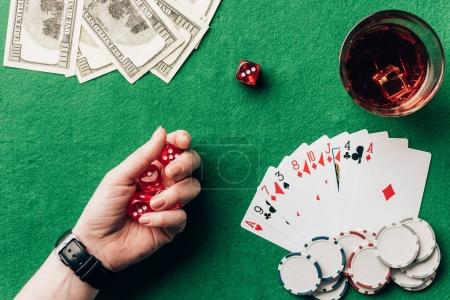 Woman holding dice by casino table with money and chips