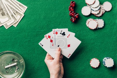 Female hand holding playing cards by casino table
