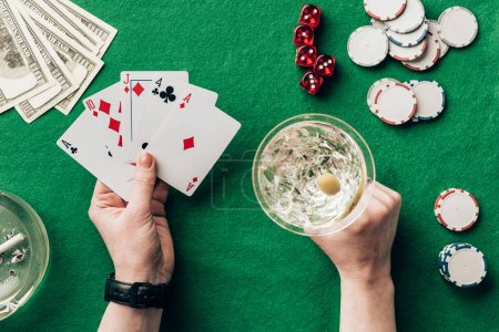 Woman with alcohol in glass playing poker game by casino table