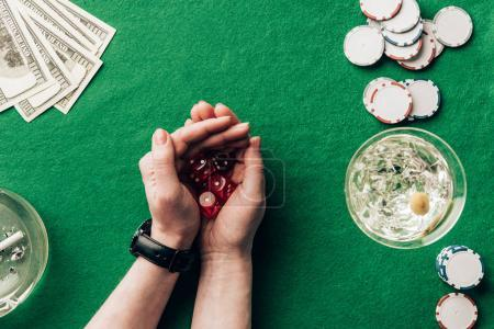 Woman playing dice game by casino table with money and chips