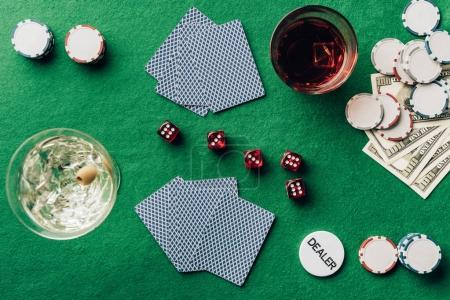 Gambling concept with alcohol on casino table with cards and dice