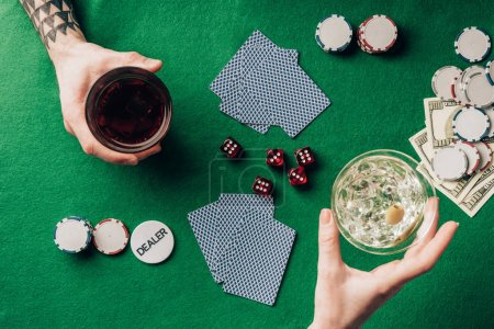 Man and woman with drinks gambling by table with dice and cards