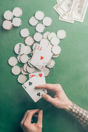 Male hand with poker cards by casino table