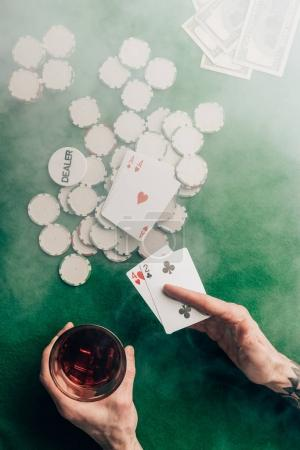 Man with whiskey and poker cards by casino table