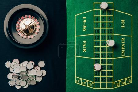 Casino table with roulette and round chips