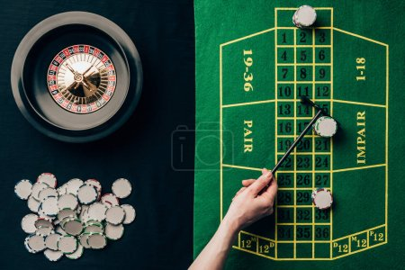 Woman moving chips on casino table with roulette