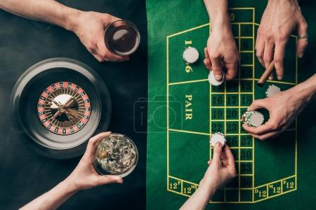 Hand with whiskey and chips by casino table with bets and roulette