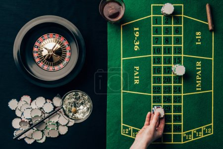Woman placing a bet on table with roulette