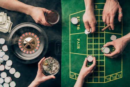 People drinking alcohol while playing roulette by casino table