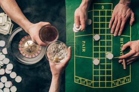 People toasting drinks while playing roulette by casino table