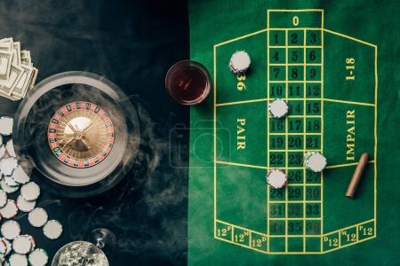 Casino table with roulette and glass with whiskey
