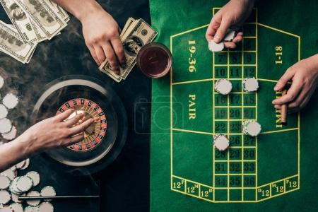 People placing bets while playing roulette on casino table
