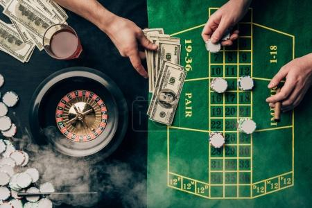 Men placing a bet on casino table with roulette