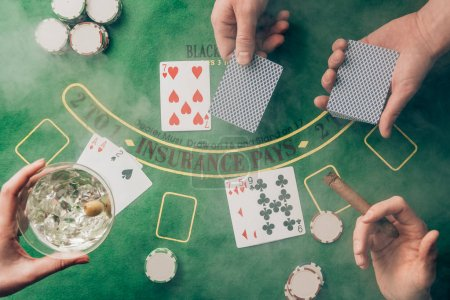 Smoke over people playing black jack by casino table with cards and chips