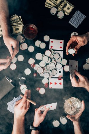 Smoke over people playing poker by casino table with cards and chips