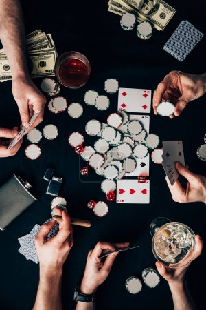 Men and woman playing poker by casino table with cards and chips