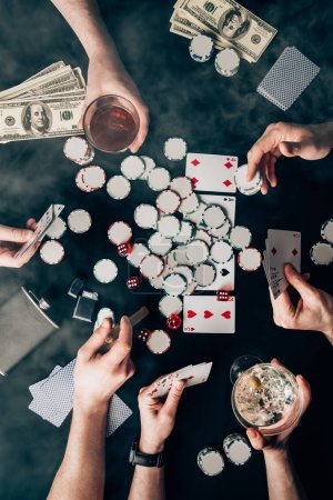 Smoke over people with alcohol in glasses playing poker by casino table with money and chips