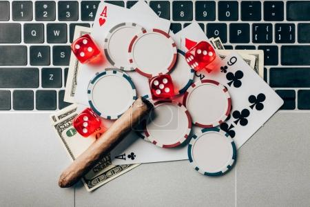 Online gambling concept with chips and money on laptop