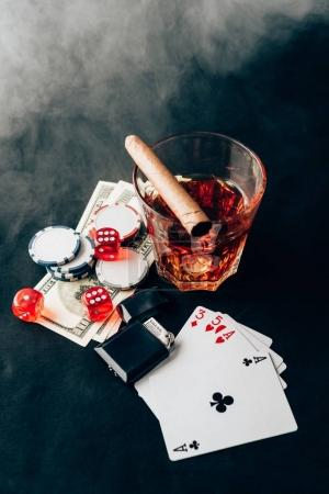 Smoke over whiskey and cigar on table with chips and money