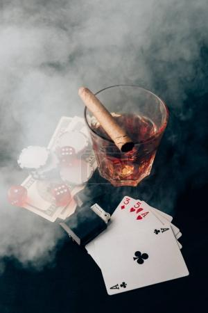 Glass with whiskey and cigar on table with cards and money