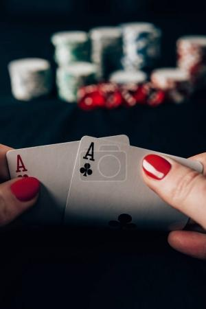 Woman playing poker game by casino table