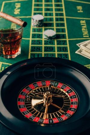 Casino table with roulette and glass with whiskey and cigar