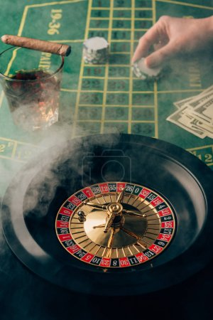Smoke over female hand placing a bet on table with roulette