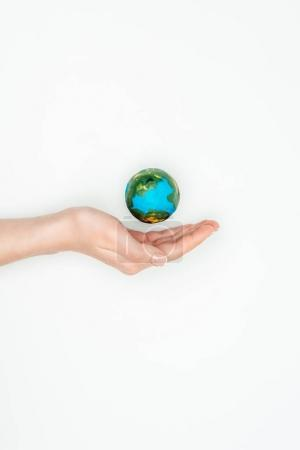 cropped image of woman holding hand near earth model isolated on white, earth day concept