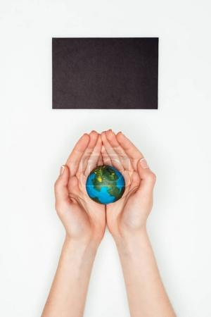 cropped image of woman holding earth model under blackboard isolated on white, earth day concept